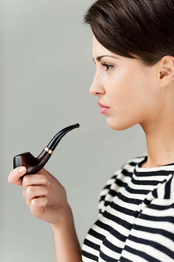 Smoking pipe. Side view of attractive young short hair woman in striped clothing holding pipe and looking away royalty free stock image