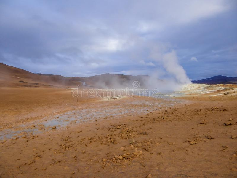 Iceland - Smoking hot pots at the geothermal activie region of Hverir. Smoking pool, filled with sulfur. Thick and dense smoke surrounding the whole area stock photography