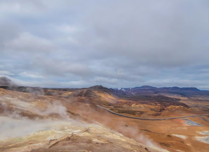 Iceland - Smoking hot pots at the geothermal activie region of Hverir. Smoking pools, filled with sulfur seen from above. Thick and dense smoke surrounding the stock photography