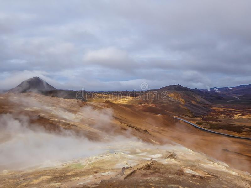 Iceland - Smoking hot pots at the geothermal activie region of Hverir. Smoking pools, filled with sulfur seen from above. Thick and dense smoke surrounding the royalty free stock photo