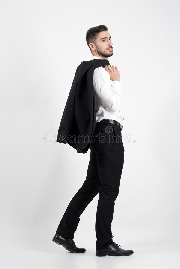 Smoking que lleva que camina del hombre lujoso elegante joven sobre su hombro que mira lejos fotos de archivo libres de regalías