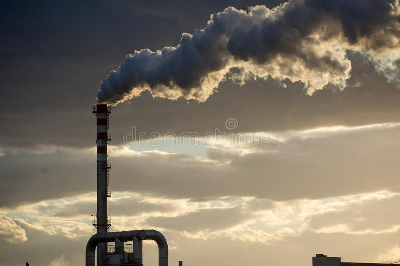 Smoking Red and White Bands Chimney On Backlight With White Smoke At Sunset. Smoking Red and White Bands Chimney On Backlight With White Smoke On Cloudy Sky stock photography