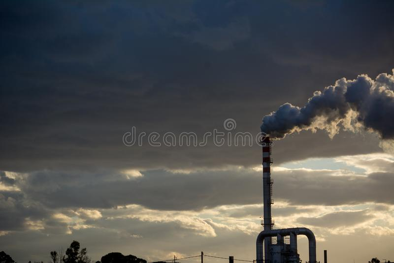 Smoking Red and White Bands Chimney On Backlight With White Smoke At Sunset. Smoking Red and White Bands Chimney On Backlight With White Smoke On Cloudy Sky royalty free stock images
