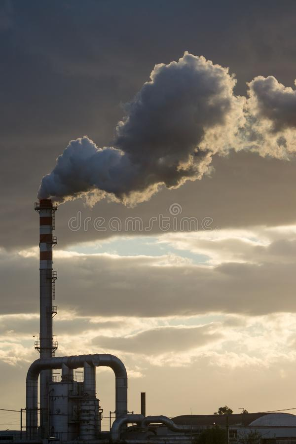 Smoking Red and White Bands Chimney On Backlight With White Smoke At Sunset. Smoking Red and White Bands Chimney On Backlight With White Smoke On Cloudy Sky royalty free stock image