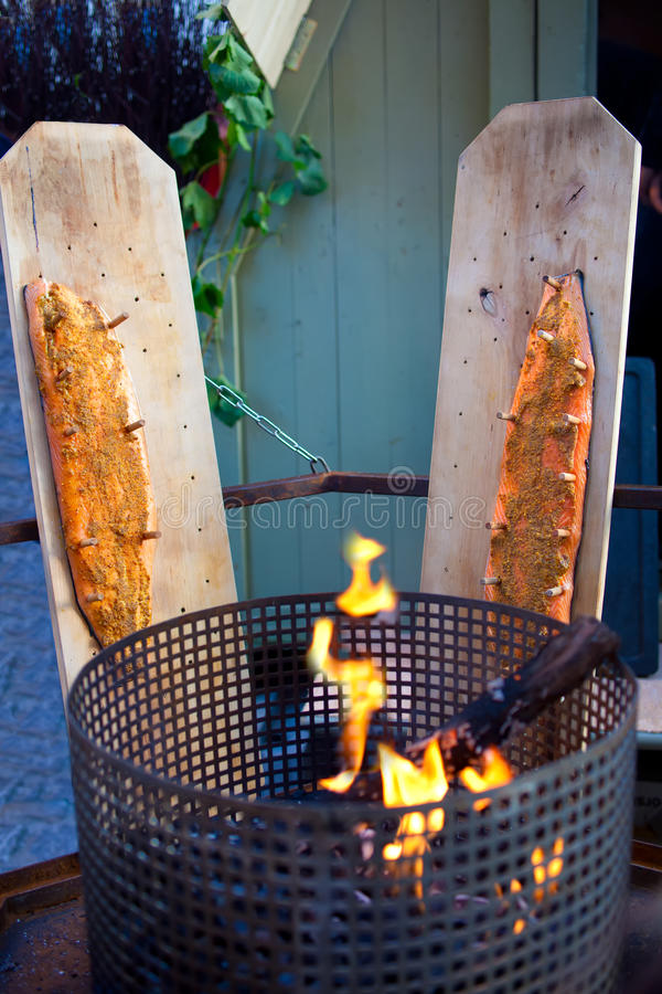 Smoking Salmon Fillets. Salmon fillets pegged out on boards alongside a brazier to smoke as it was traditionally done in the Middle Ages royalty free stock image