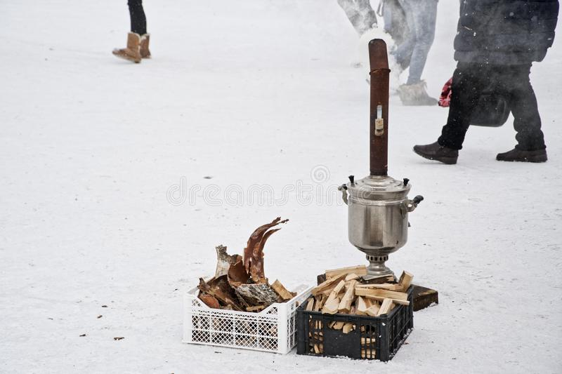 Smoking samovar on the street in the snow in winter. Help freezing people. Traditions of mercy in Siberia stock photos