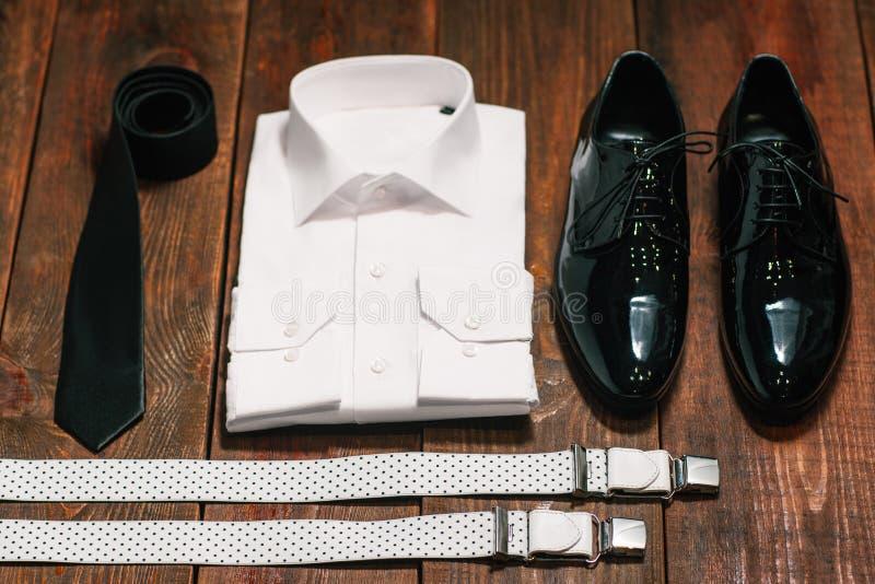Smoking skor för patenterat läder, hängslen, en vit skjorta royaltyfria bilder