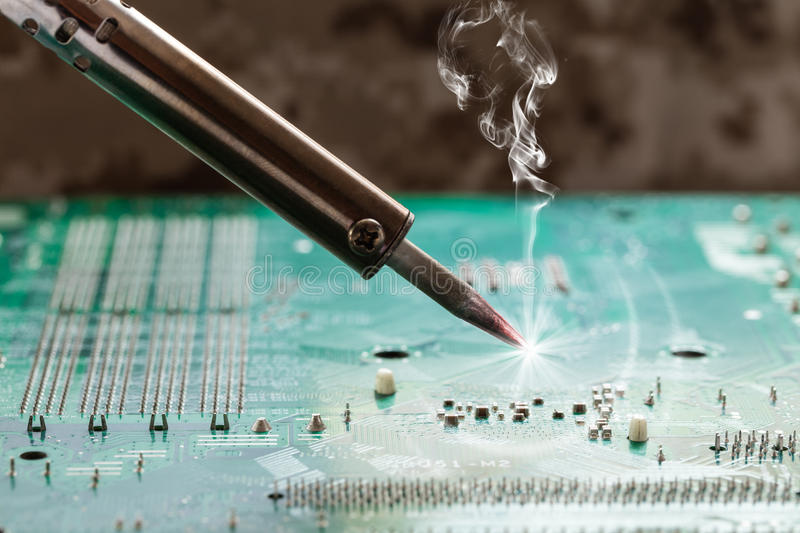 Smoking soldering iron stock photos