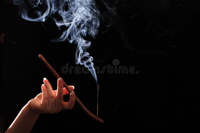 Smoking stick in the woman`s hand. On black background royalty free stock images