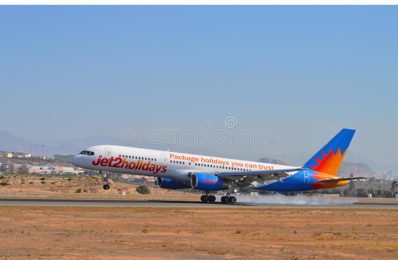 Jet2 Holidays Aircraft Passenger Plane Smoking Tyres At Alicante Airport. A passenger plane smokes its tyres as it touches down safely onto the runway at royalty free stock photo