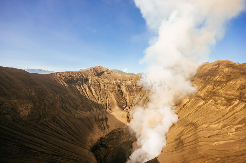 Smoking volcano Mt.Bromo in sunrise. Mt.Bromo and fog in the morning. Photo from Bromo Tengger Semeru National Park, Surabaya, East Java, Indonesia royalty free stock photography