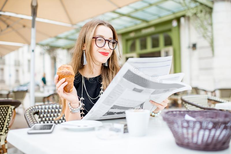 Smoking woman at the french cafe. Young woman reading newspaper during a breakfast with croissant sitting outdoors at the typical french cafe terrace in France royalty free stock photo