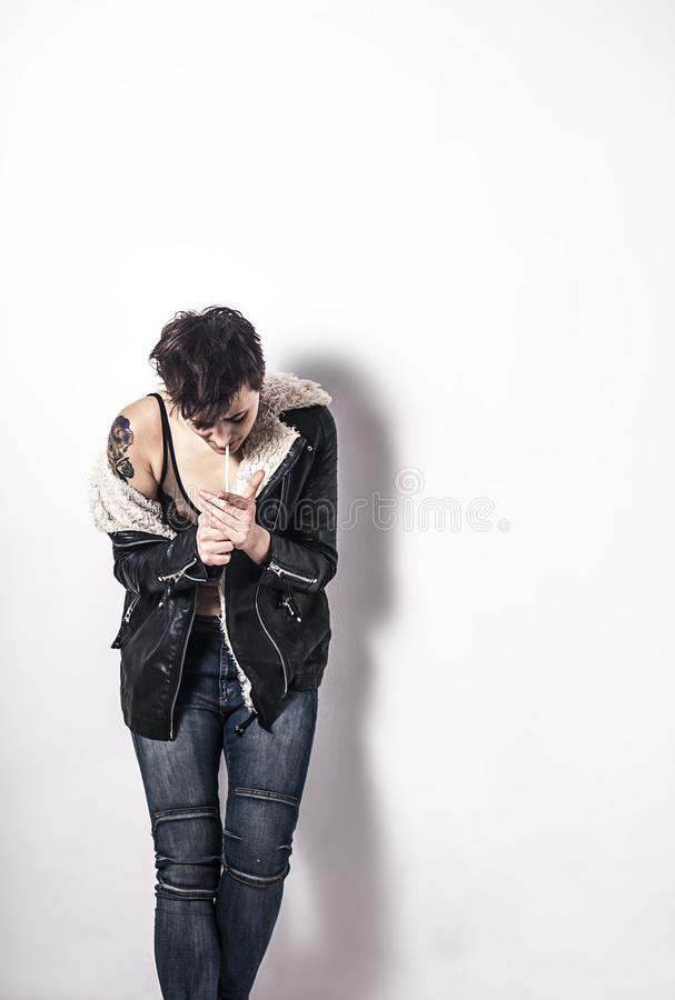 Smoking woman with short balck hair. And black leather jacket royalty free stock images