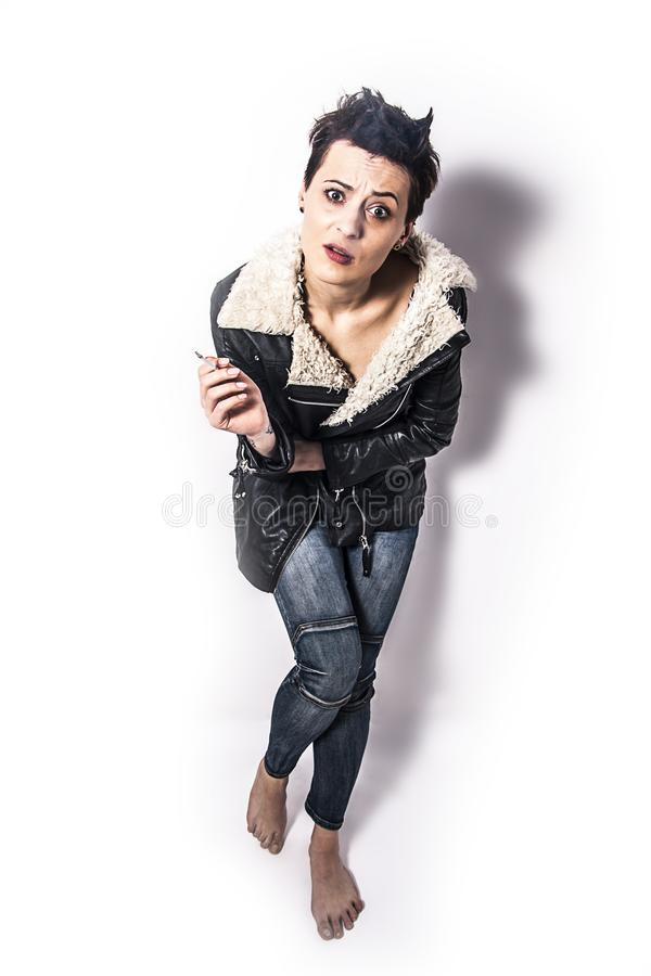 Smoking woman with short balck hair. And black leather jacket stock photo
