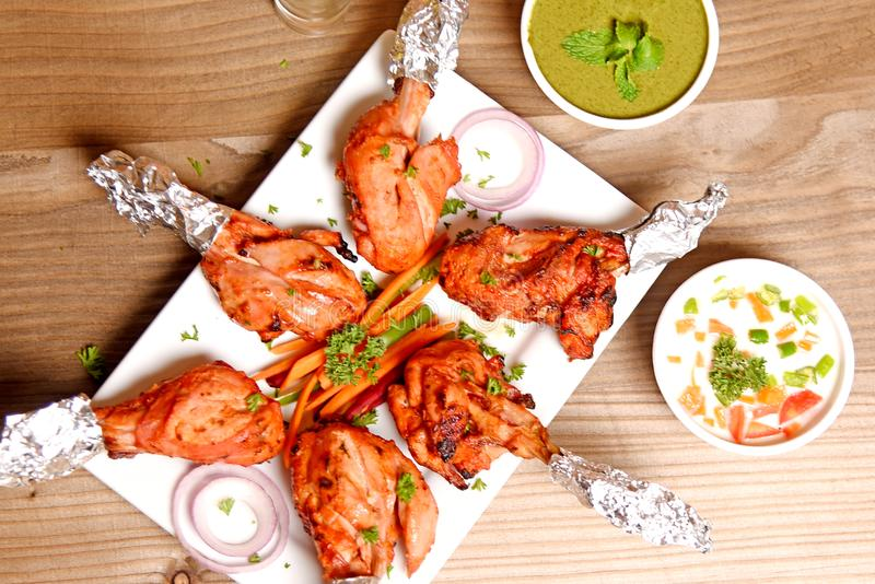 Chicken Tandoori. Smoky and juicy chicken cooked in exotic spices in a tandoor stock images