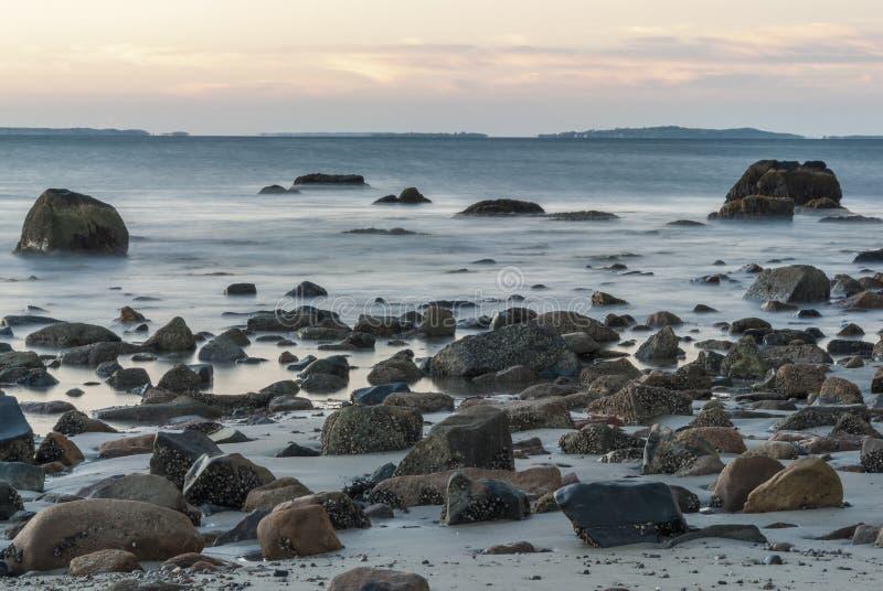 Smoky motion blur rocky Buzzards Bay beach stock image