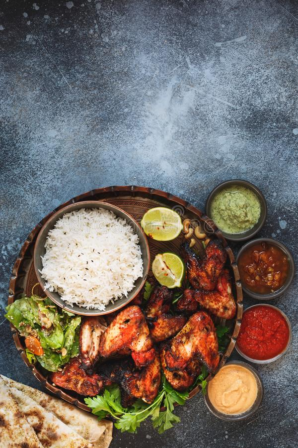Smoky, roasted tandoori chicken wings served with different chutney dipping sauces. Smoky, roasted tandoori chicken wings served with pilau rice , soft garlic royalty free stock photo