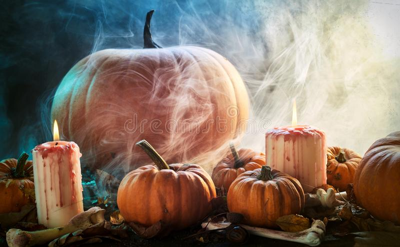 Smoky spooky Halloween background. Of fresh pumpkins, dried bones, leaves and burning candles in a smoky atmospheric forest outdoors with copy space royalty free stock images
