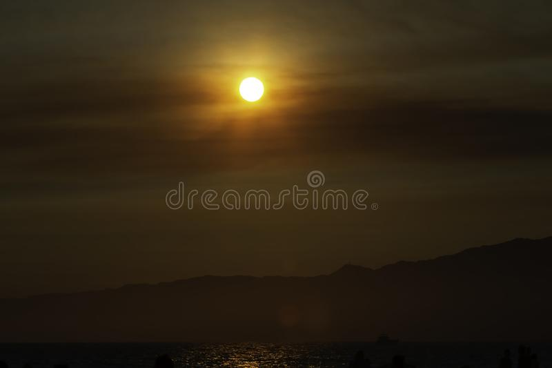 Smoky sunset over mountains in Santa Monica California. Sun covered with clouds over the mountains in Los Angeles stock image