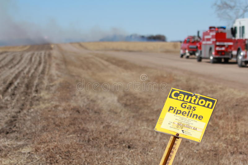 Smoldering Field. Cornfield smoldering after the gas line fire was put out with the fire department on standby. Natural gas line warning in foreground in Hooper royalty free stock images