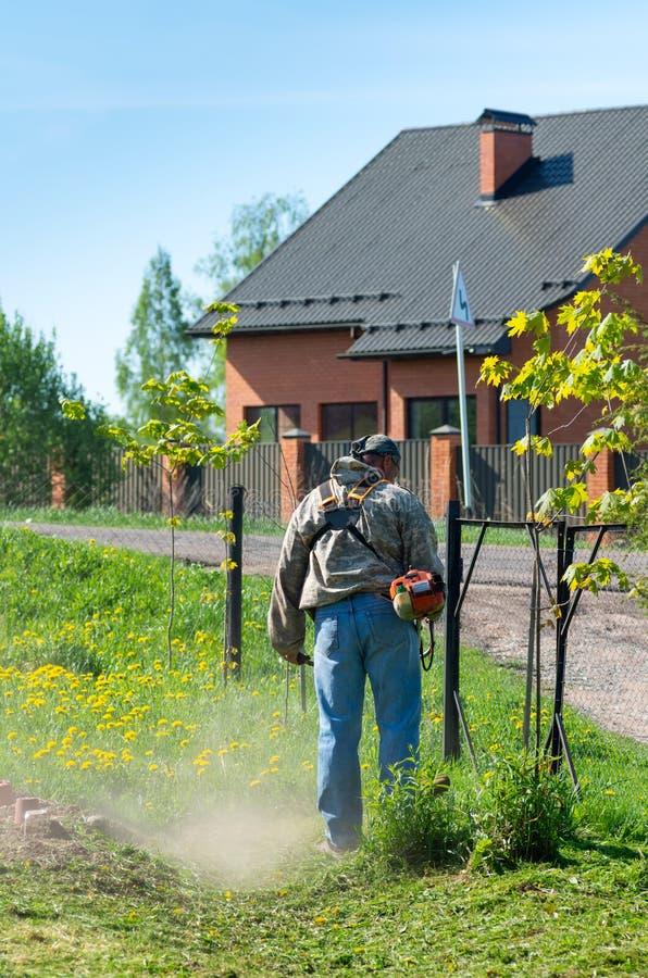 Smolensk, Russie - peuvent 12, 2018 : l'homme avec une tondeuse à gazon manuelle fauche l'herbe photo libre de droits