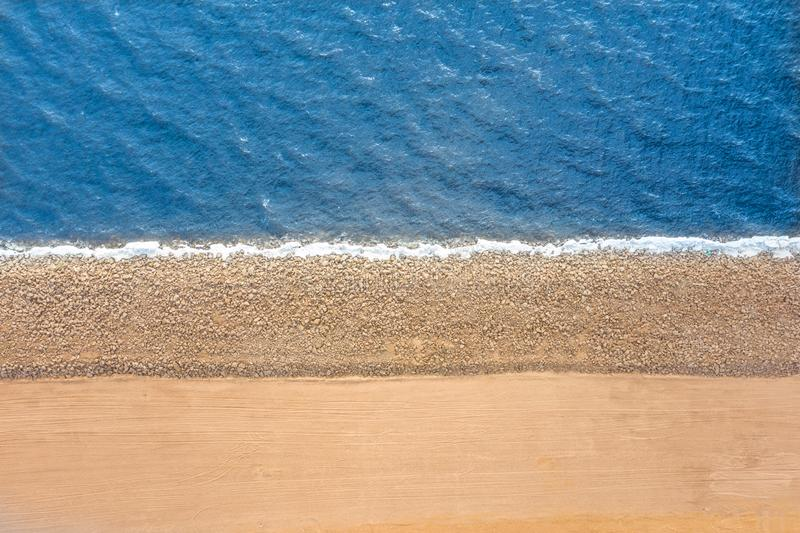 Smooth border between sea and land. Stones mound of sand and water, top aerila view stock photos