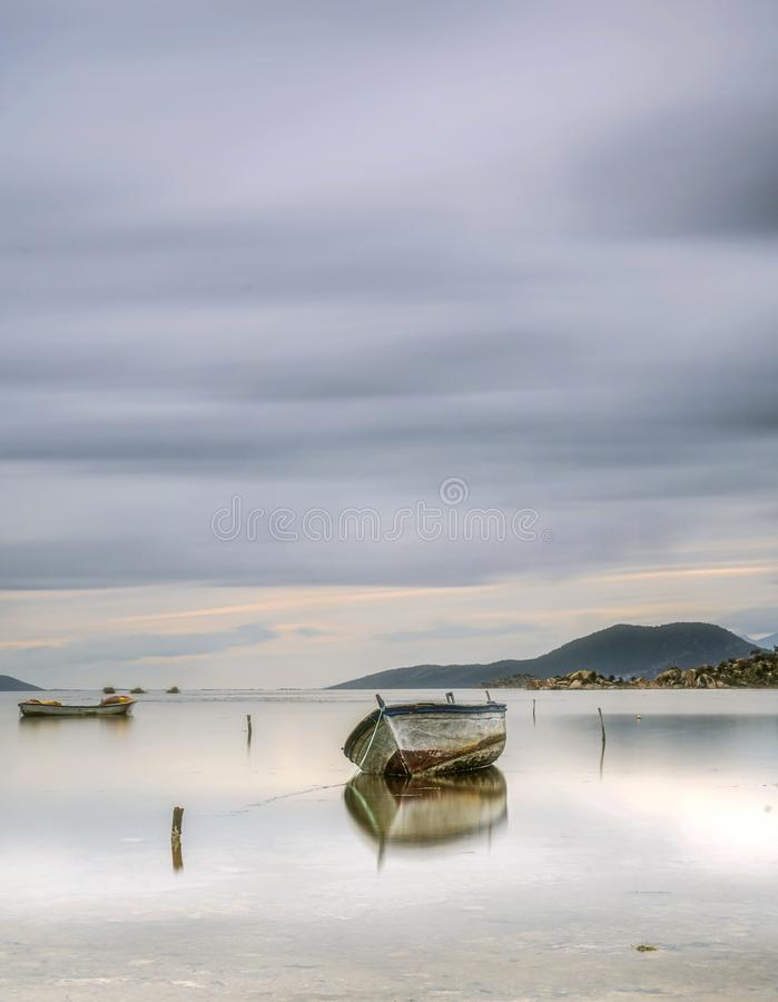 Turkey aydin long exposure blue clouds and a boat on a lake royalty free stock images