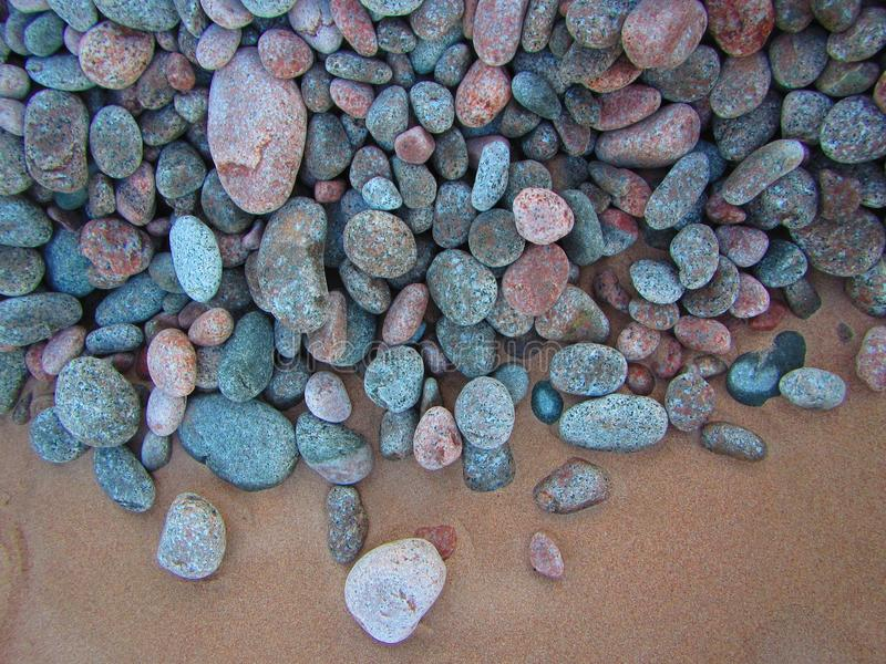 Smooth colourful stones and sand royalty free stock photo
