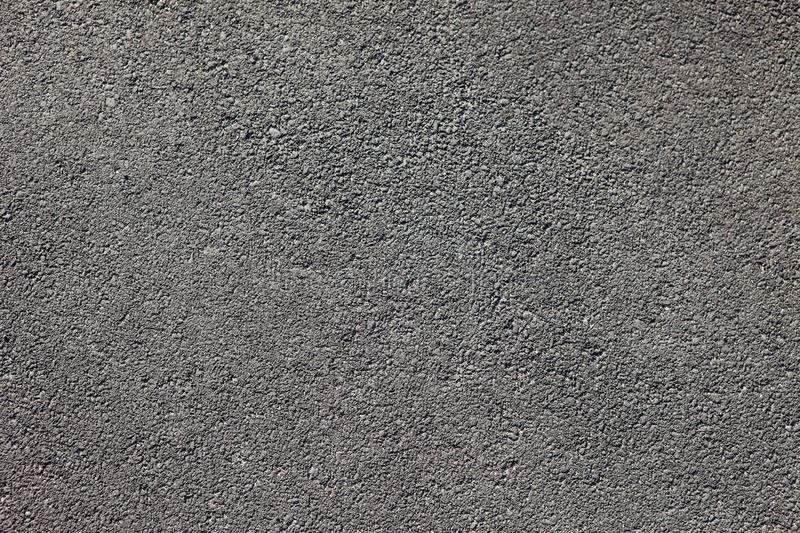 Smooth dark grey asphalt pavement texture with small rocks stock images