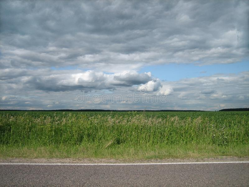 Smooth edge of paved roads in a clean green field in the countryside royalty free stock photo
