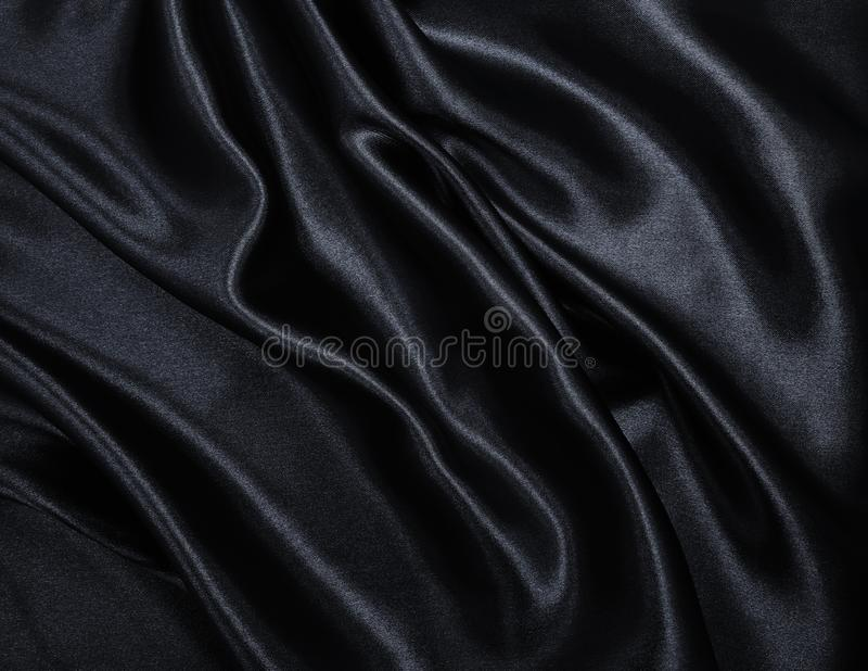 Smooth elegant black silk or satin texture as abstract background. Luxurious background design. Smooth elegant black silk or satin texture can use as abstract royalty free stock photography