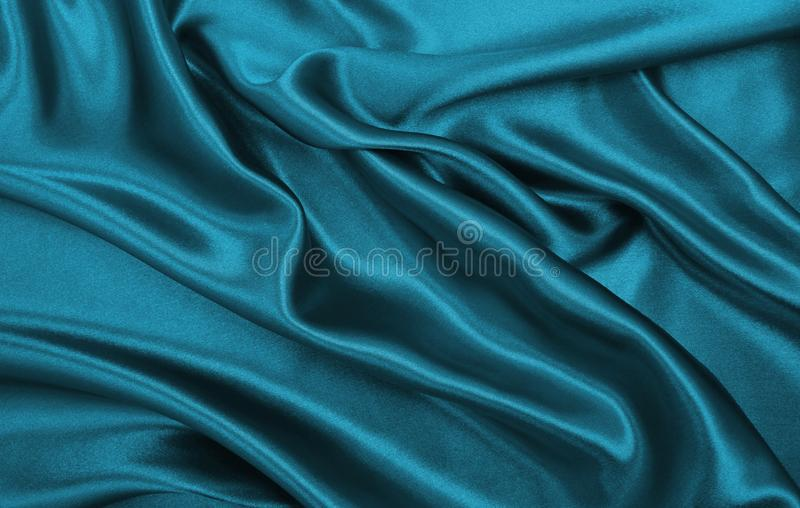 Smooth elegant blue silk or satin luxury cloth texture as abstract background. Luxurious Christmas background or New Year. Smooth elegant blue silk or satin stock photography