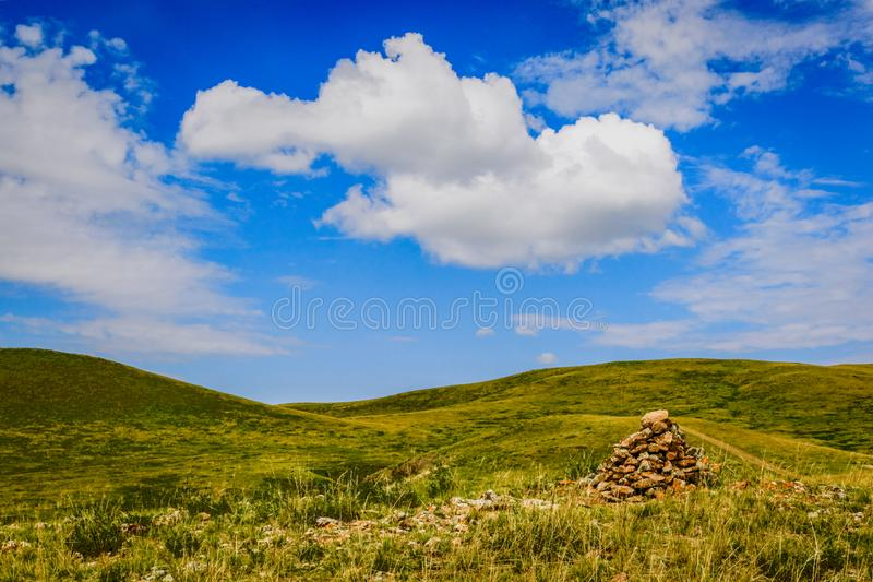 Smooth rolling hills with a pile of red rocks to the right, bright blue sky in Inner Mongolia China. Smooth green rolling hills with a pile of red rocks to the royalty free stock photos