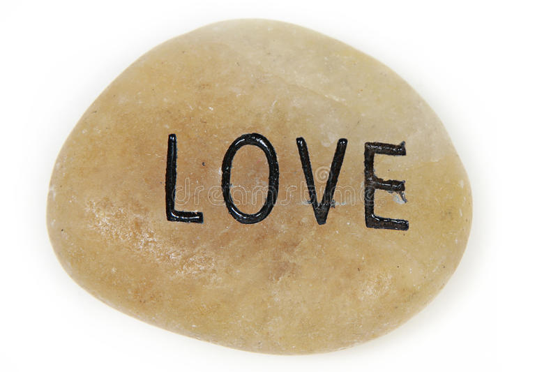 Smooth love stone. A closeup of a smooth stone with the word love engraved and painted on it. White background royalty free stock images