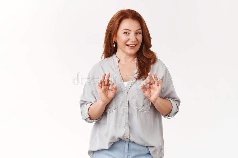 Smooth nice. Good-looking stylish middle-aged redhead woman give positive feedback recommend service smiling happily stock photography