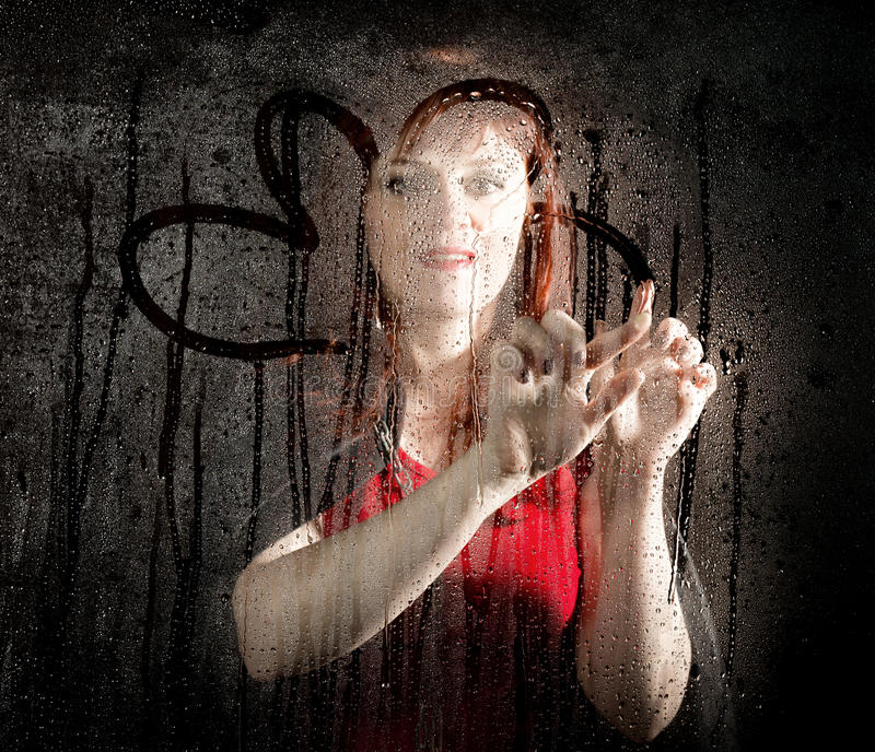 Smooth portrait of female model, posing behind transparent glass and painting on water drops. young smiling woman stock image