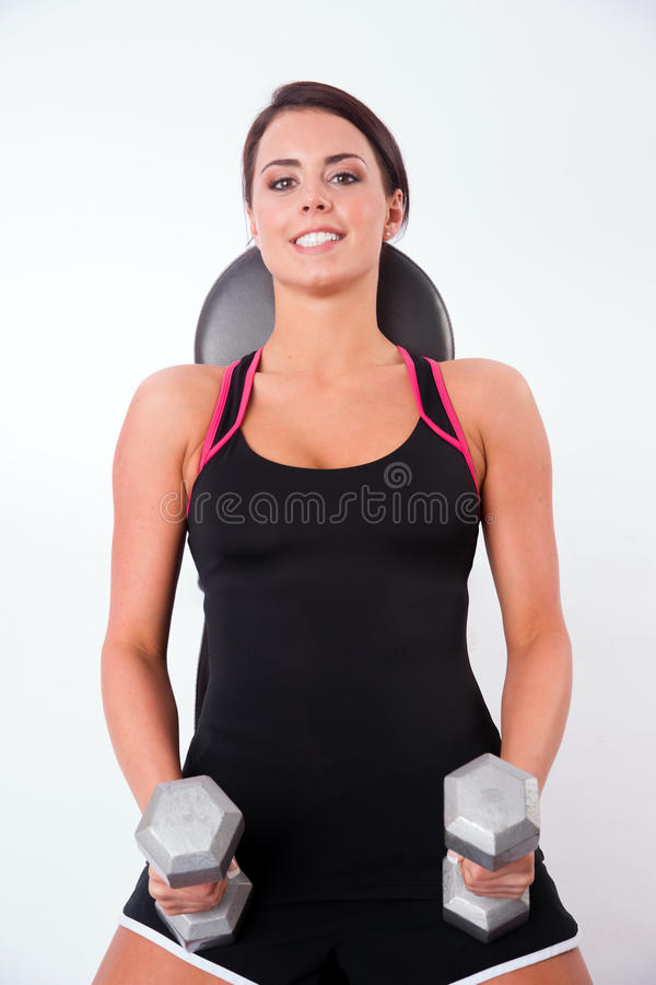 Smooth Skin Beautiful Brunette Woman Working Out Weight Bench. Young adult woman tones her muscle on the weight bench royalty free stock images