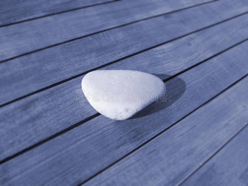 Smooth stone on wood. Smooth white stone on wooden table surface stock photography