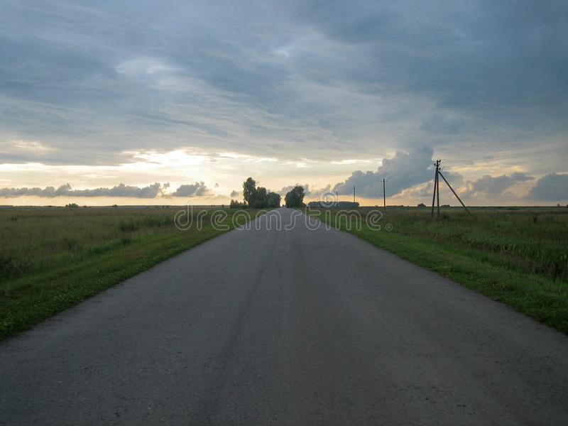 Smooth straight asphalt road in the countryside under the sky with clouds at sunset. Empty roads in the evening. The sun painted the sky with a sunset light royalty free stock photo