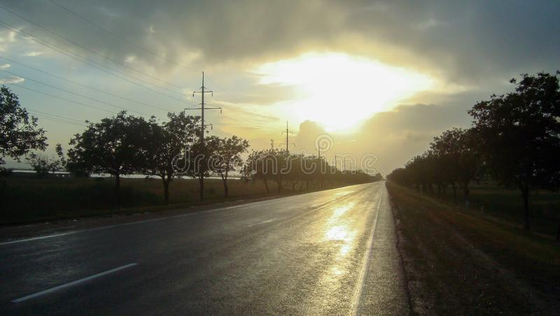 Smooth straight asphalt road in the countryside under the sky with clouds at sunset. Empty roads in the evenings. The sun painted the sky with a sunset light royalty free stock photo