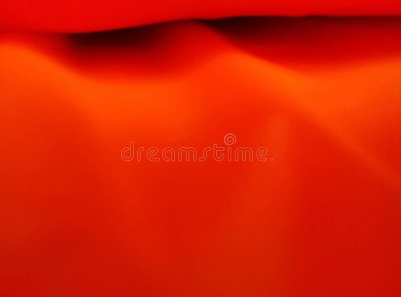 Smooth surface of corrugated satin fabric. Soft texture red fabric. Abstract, art, background, blank, blur, blurred, blurry, bright, bumpy, clothes, color royalty free stock image