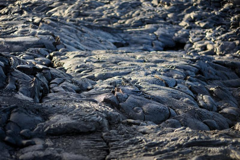 Smooth, undulating surface of frozen pahoehoe lava. Frozen lava wrinkled in tapestry-like folds and rolls resembling twisted rope. On Big Island of Hawaii, USA royalty free stock photos