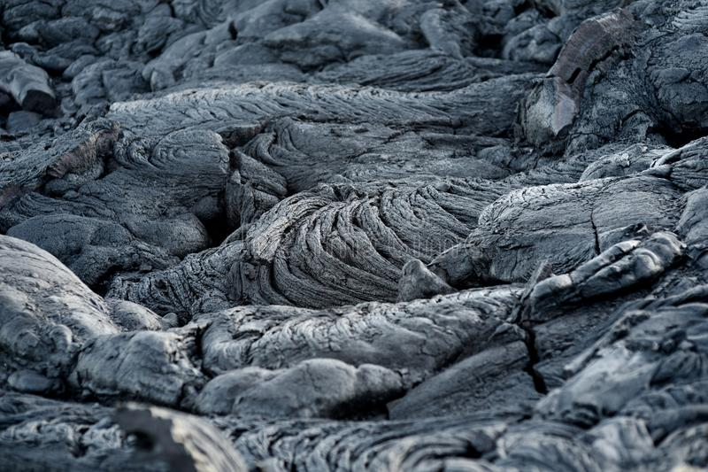 Smooth, undulating surface of frozen pahoehoe lava. Frozen lava wrinkled in tapestry-like folds and rolls resembling twisted rope. On Big Island of Hawaii, USA royalty free stock photography