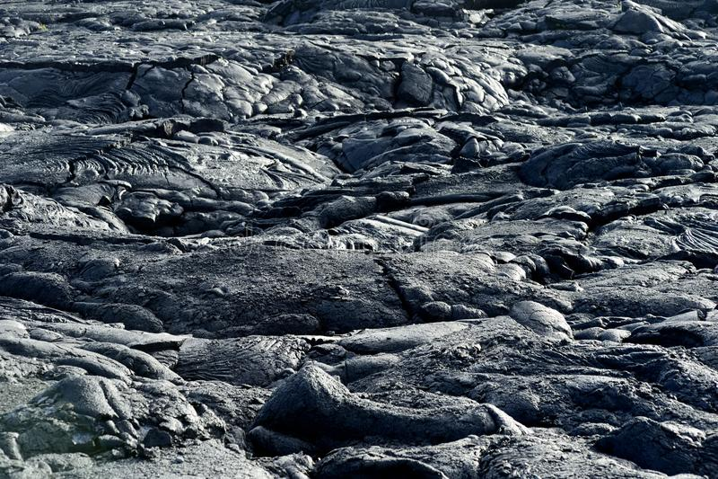 Smooth, undulating surface of frozen pahoehoe lava. Frozen lava wrinkled in tapestry-like folds and rolls resembling twisted rope. On Big Island of Hawaii, USA royalty free stock photo
