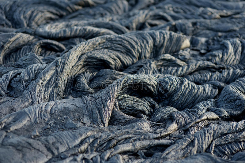 Smooth, undulating surface of frozen pahoehoe lava. Frozen lava wrinkled in tapestry-like folds and rolls resembling twisted rope. On Big Island of Hawaii, USA stock images