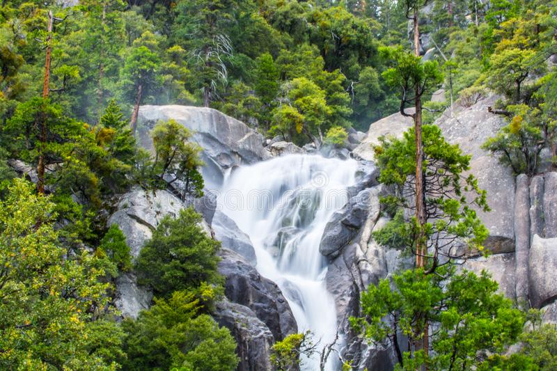 Trickling waterfall at Yosemite National Park. Smooth waterfall trickling down the sides of a mountain heading downward towards a stream royalty free stock photos