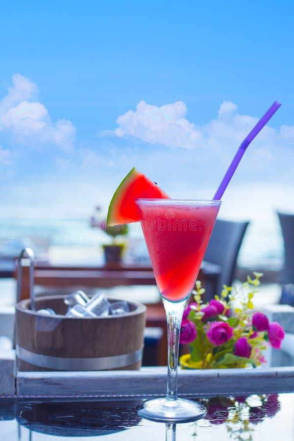 Smoothie арбуза, соки арбуза установил на таблицу на пляже стоковое изображение rf