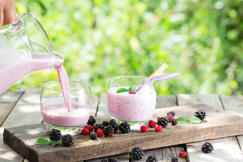 Smoothie или йогурт ягоды лить от кувшина в стекло стоковое фото