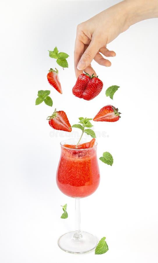 Smoothie клубники и падая части ягод и sprigs мяты в стекле Левитация, изолированные объекты на белой предпосылке стоковые фото