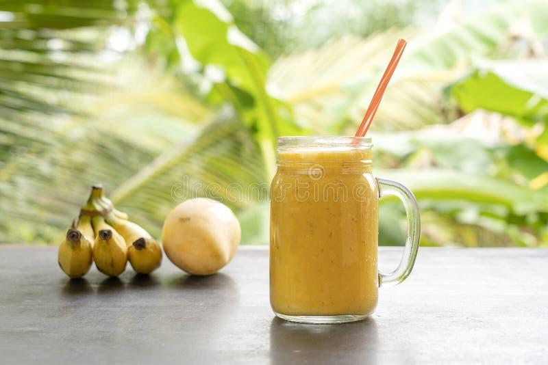 Smoothie с тропическими плодами: манго, банан, ананас в стеклянном опарнике на деревянном столе r стоковая фотография
